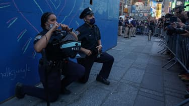 Deux policiers mettent leur genou à terre sur la célèbre place Time Square, à New York, en solidarité avec les manifestants, le 31 mai.