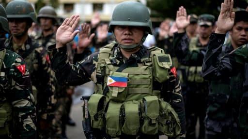 Des soldats philippins participent au hissage du drapeau à Marawi, dans le sud, le 12 juin 2017