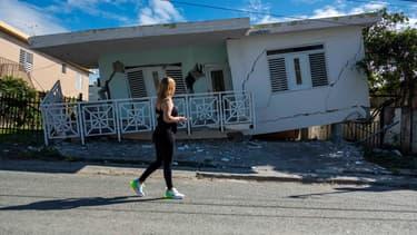 Une femme passe devant une maison endommagée par le premier séisme de magnitude 5.8 qui a touché Porto Rico lundi 6 janvier, avant le séisme de mardi 7 janvier