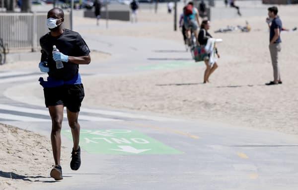 Un jogger avec un masque à Venice Beach en Californie (Etats-Unis) le 21 mars 2020