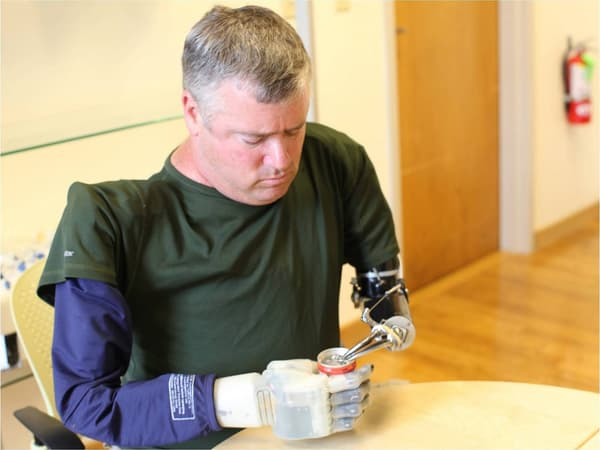 """This handout photo obtained from the US Defense Advanced Research Projects Agency(DARPA) on September 14, 2015 shows a volunteer amputee fitted with an experimental prosthetic hand that lets him """"feel"""" sensations, holding a soada can. After six years of development, the Revolutionizing Prosthetics program developed two anthropomorphic advanced modular prototype prosthetic arm systems, including sockets, which offer increased range of motion, dexterity and control options. The Revolutionizing Prosthetics program is ongoing and aims to continue increasing functionality of the DARPA arm systems so servicemembers with arm loss may one day have the option of choosing to return to duty. Additionally, the dexterous hand capabilities developed under the program have already been applied to small robotic systems used in manipulating unexploded ordnance, thus keeping soldiers out of situations that have led to limb loss prothèse"""