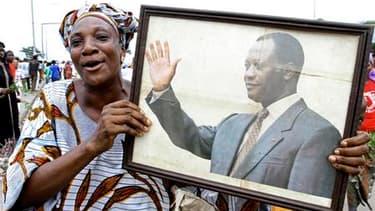 Une manifestante brandit un portrait d'Alassane Ouattara à Abobo, quartier d'Abidjan en proie aux violences post-électorales. Des milliers de femmes ont manifesté mardi dans plusieurs quartiers de la capitale économique de la Côte d'Ivoire pour réclamer l