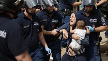 Une migrante cerclée de policiers tente de se débattre, son enfant dans les bras, le 3 septembre, à Bicske, en Hongrie.