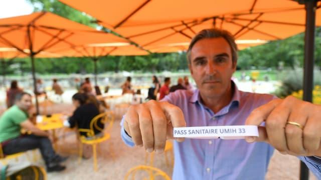 Le président de l'UMIH-33, Laurent Tournier montre un bracelet pass sanitaire au restaurant L'Orangerie, le 18 août 2021 à Bordeaux
