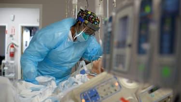 Une soignante au chevet d'un patient dans un département des malades du Covid-19.