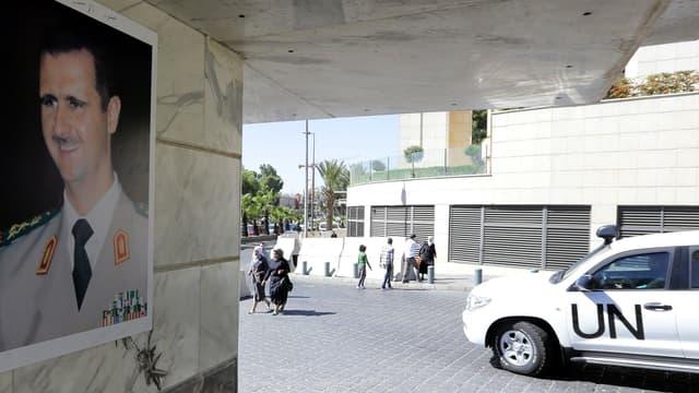 Un véhicule des Nations unies transportant des inspecteurs de l'OIAC passe devant un portrait de Bachar al-Assad, le 9 octobre 2013, à Damas.