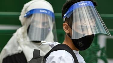 Des personnes portant des visières de protection dans un centre de tests du Covid-19 à Srinagar, dans le Cachemire indien, le 16 juillet