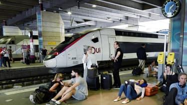 Des voyageurs attendent sur un quai de la gare Montparnasse le 27 juillet 2018, à Paris.