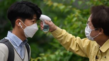 Un homme contrôle la température d'un étudiant à Séoul (Corée du Sud), en raison des craintes liées au coronavirus, le 20 mai 2020.