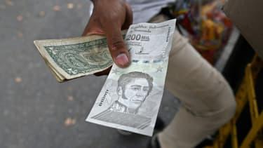 Un billet de 200.000 bolivars à côté de billets de 1 dollar américain dans une rue de Caracas, le 14 avril 2021 au Venezuela