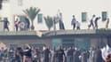 Manifestants sur le toit d'un bâtiment de l'ambassade des Etats-Unis à Tunis. Trois personnes au moins ont été tuées et 28 autres blessées vendredi à Tunis lors d'affrontements avec la police tunisienne aux abords et à l'intérieur de l'ambassade américain