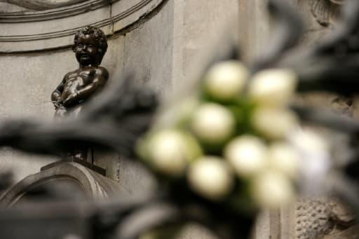 Des fleurs déposées au pied de la statue du Manneken Pis, au lendemain des attentats de Bruxelles, le 23 mars 2016