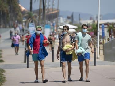 Des promeneurs avec les masques le long de la plage à Barcelone, le 18 juillet 2020