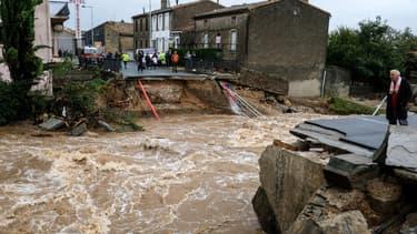 Des habitants se tiennent devant ce qui était auparavant un pont à Villegailhenc, dans l'Aude, après de violentes inondations le 15 octobre 2018.