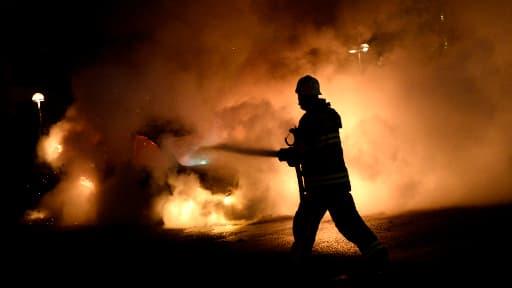 A Stockholm, secouée par des émeutes depuis cinq jours, un pompier maîtrise un incendie, mercredi soir.