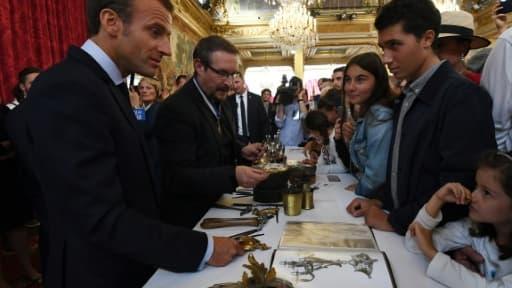 Le président Emmanuel Macron (G) rencontre des jeunes visiteurs à l'Elysée, lors des journées du patrimoine, le 15 septembre 2018
