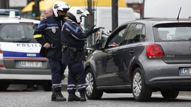 Des policiers verbalisent un contrevenant à la circulation alternée, ce lundi à Paris.