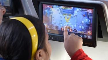 Une petite fille joue sur un écran tactile, en 2017. (Photo d'illustration)