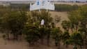 """L'un des drones de Google au beau milieu d'une livraison, au moment de """"déposer"""" le colis."""