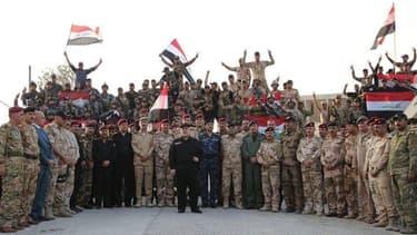 Des soldats irakiens prennent la pose et fêtent leur victoire à Mossoul, aux côtés du Premier ministre Haider al-Abadi, sur une photo diffusée le 10 juillet 2017.