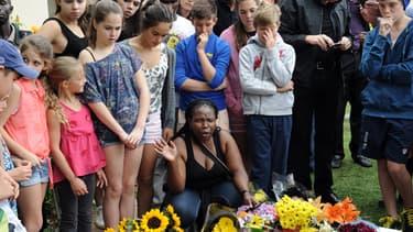 """Des anonymes rendent hommage à """"Maniba"""" devant sa maison de Johannesburg, au lendemain de sa mort."""