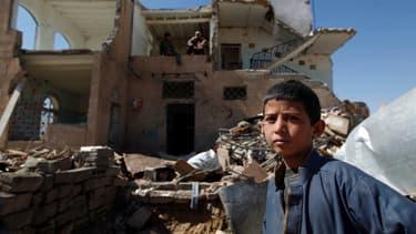Un enfant se tient devant une maison détruite par les frappes de la coalition, le 14 novembre 2016.