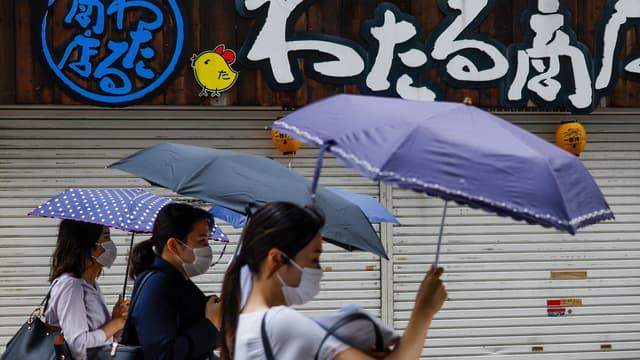 Des personnes se protègent de la pluie alors que la tempête tropicale Nepartak s'approche du Japon (photo d'illustration)