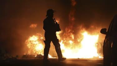 Un policier près d'un véhicule en feu à La Réunion ce lundi, lors des violences survenues en marge des gilets jaunes. .