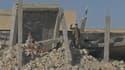 Un milicien chiite fait le signe de la victoire sur les ruines du tombeau de Saddam Hussein.