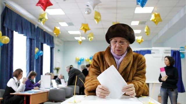 Dans un bureau de vote de Moscou. Vladimir Poutine s'imposera probablement sans difficulté dès le premier tour de l'élection présidentielle qui s'est ouvert dimanche dans l'Extrême-Orient russe, malgré les doutes de l'opposition quant à la légitimité du s