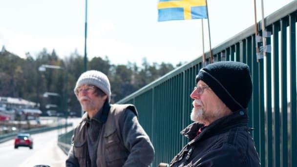 Pontus Berglund (g) et son frère jumeau Ola bavardent, l'un en Suède, l'autre en Norvège, sur le pont reliant les deux pays, le 1er mai 2021 à Svinesund