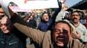 Des partisans du président Hosni Moubarak rassemblés près de la place Tahrir, au Caire, où s'était à nouveau massée mardi une foule d'opposants au régime. Des heurts ont éclaté entre les deux camps mardi. /Photo prise le 2 février 2011/REUTERS/Yannis Behr