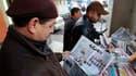 Un homme découvre la composition du nouveau gouvernement dans un journal tunisien devant un kiosque du centre de Tunis. Le remaniement annoncé jeudi pour écarter les caciques du régime de Zine ben Ali semble avoir quelque peu calmé apaisé les manifestants