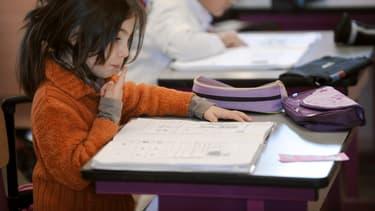 Petite fille en classe de CP devant le casse-tête de la lecture.