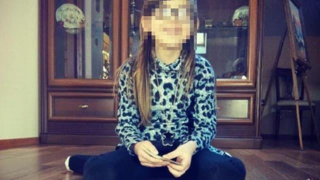Berenyss a 7 ans, a les cheveux bruns longs, et porte une jupe à volants blancs et un haut multicolore.