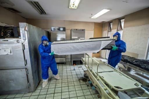 Des employés de Los Olivos Funerales en combinaison intégrale de protection transportent du corps d'une personne décédée du coronavirus, le 1er juin 2020 à Mexico