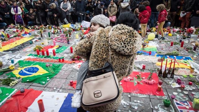 Une mère portant son enfant se recueille en Belgique au lendemain des attentats qui ont frappé Bruxelles.