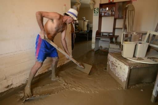 Le 19 mars 2017, un habitant tente d'évacuer la boue de chez lui à Huarmey, à 300 km au nord du Pérou, encerclée par la boue depuis les pluies diluviennes qui ont balayé le pays ces derniers jours
