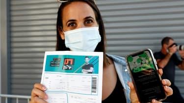 """Une femme à Tel-Aviv montrant son """"passeport vert"""", un permis octroyé par les autorités israéliennes aux personnes ayant reçu deux doses du vaccin ou guéri du Covid-19 pour avoir accès à certains lieux et événements publics, 5 mars 2021"""