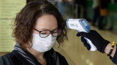 Une femme se fait prendre sa température à Hong-Kong, le 17 mars 2020. (PHOTO D'ILLUSTRATION)