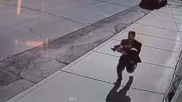 Une caméra de vidéosurveillance a capté la fuite de l'homme, avec un enfant dans les bras.