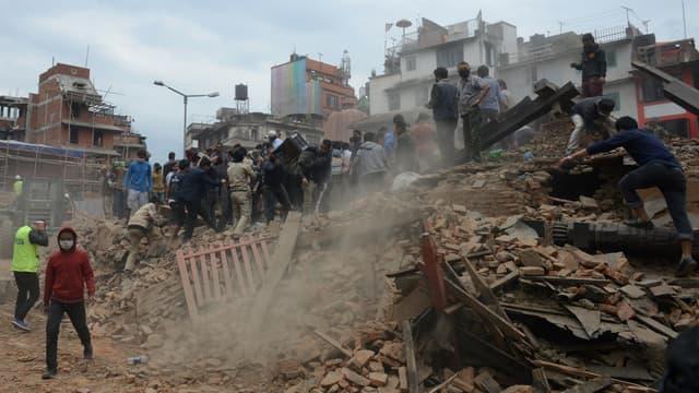 Des hommes évacuent les décombres à Katmandou, après le violent séisme qui a frappé le Népal samedi 25 avril 2015.