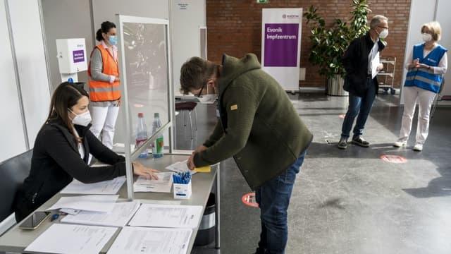 Un employé du groupe de chimie Evonik remplit un formulaire pour se faire vacciner contre le Covid-19 sur son lieu de travail, le 19 mai 2021 à Hanau, en Allemagne