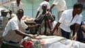 Des soldats et des secouristes transportent le corps d'un député. Des hommes en uniforme de l'armée ont attaqué mardi un hôtel de Mogadiscio, non loin du palais présidentiel, tuant au moins 31 personnes dont six députés. L'attaque a été revendiquée par le