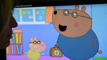 """Une passante à Londres devant un écran montrant un épisode du dessin animé britannique """"Peppa Pig"""", le 12 décembre 2017"""