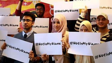 """Des musulmans se mobilisent à travers le monde contre les actions de l'Etat islamique, brandissant des pancartes avec l'inscription #Notinmyname (""""Pas en mon nom"""")."""