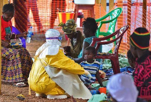 Un employé de Médecins sans frontières (MSF) nourrit un enfant victime du virus Ebola, le 15 août 2014 à Kailahun, au Sierra Leone