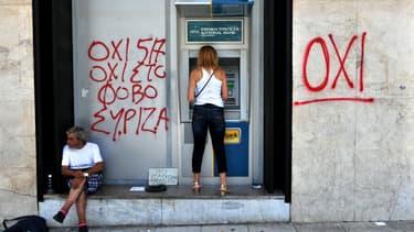 """Une femme retirant de l'argent à un distributeur à côté duquel est marqué via un tag """"OXI"""" (Non) (Image d'illustration)"""