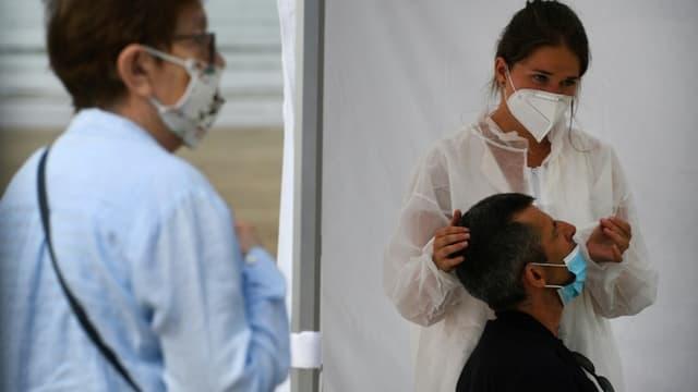 Une infirmière fait un prélèvement sur un patient dans un centre mobile de dépistage du coronavirus, sur la plage de Pentrez à Saint-Nic, dans l'ouest de la France le 12 août 2020