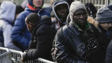 Des migrants patientent devant la plateforme d'accueil des réfugiés de l'ONG Terre d'Asile à Paris, le 26 janvier 2017